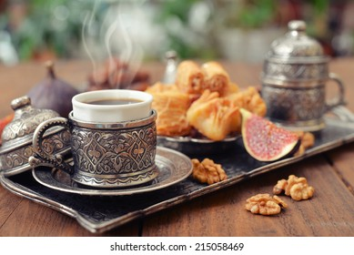 Cup of coffee with baklava on metal oriental tray