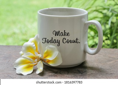A cup of coffee with Bali frangipani flower on the wooden table with inspirational motivational quote on it - Make today count, on green garden background. Morning coffee concept.