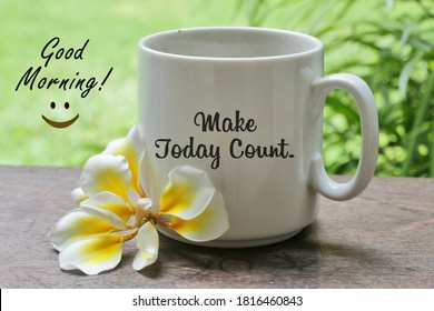 A cup of coffee with Bali frangipani flower on the wooden table with inspirational motivational quote on it - Make today count. With good morning  text greeting and an happy smiling sign.