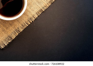 A cup of coffee and coffee bean grain on sack fabric put on black wood table background include copyspace for add text or graphic