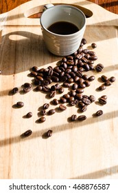 a cup of coffee and coffee bean on wooden plate in window light