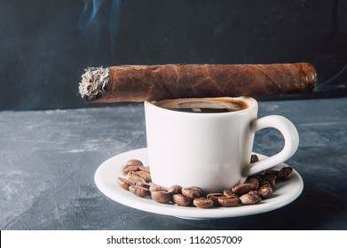 Cup of coffee, coffee beans, ashtray with cigar on dark background.Turk for coffee,aromatic coffee