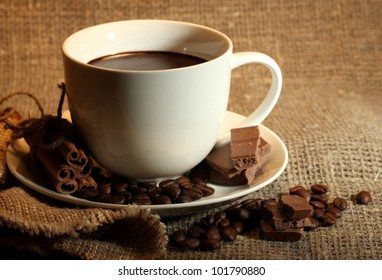 cup of coffee, beans and chocolate on sacking background
