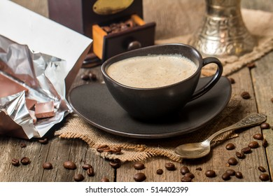 Cup of coffee with coffee beans and chocolate on wooden table