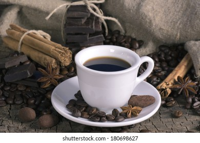 Cup of coffee with coffee beans, chocolate and spices on a wooden surface