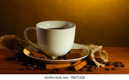 cup of coffee and beans, cinnamon sticks and chocolate on wooden table on brown background