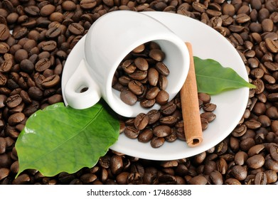 Cup with coffee beans, close up with cinnamon