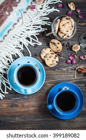 The cup of coffee, coffee beans and cookies-hearts related together on  wooden table.