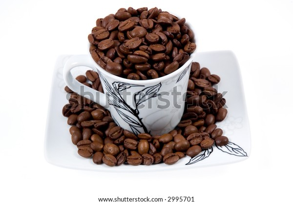 Cup with coffee beans isolated on white.