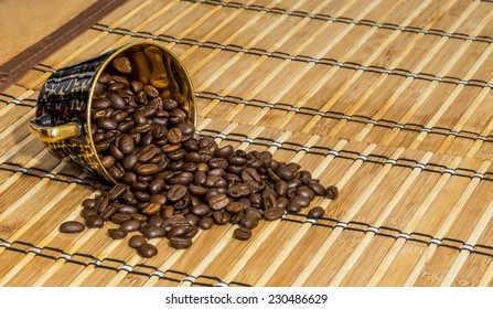 Cup of coffee beans on bamboo mat
