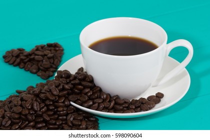 A cup of coffee beans on the blue wood background