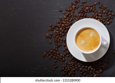cup of coffee and coffee beans on dark background, top view