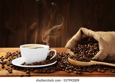 Cup of coffee with beans on table