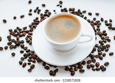 Cup of coffee and beans on white background, top view