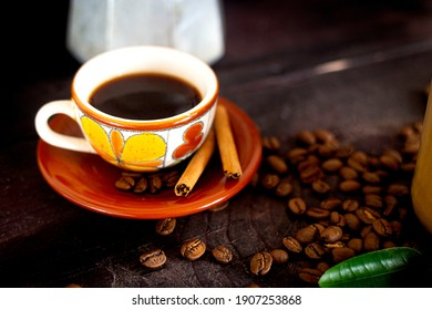 Cup of coffee with coffee beans on a wood table, close up photo