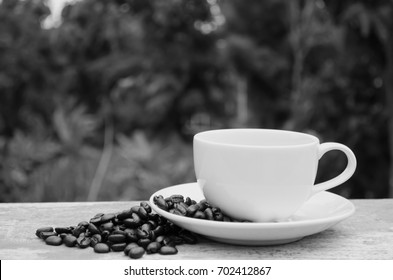 Cup of coffee and coffee beans on wood table with nature background.