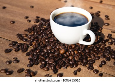A cup of coffee and coffee beans on wooden table