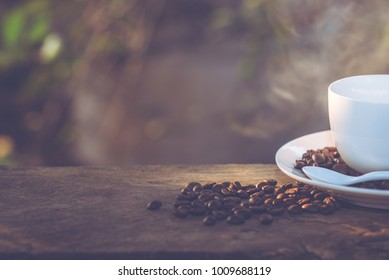 A cup of coffee and coffee beans on wooden table with the backdrop of the light of the sun / selective focus.