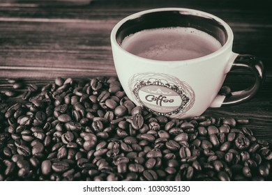 Cup of coffee and coffee beans on a wooden background