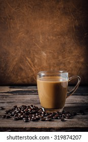 cup coffee and coffee beans on wooden floor with brown leather background