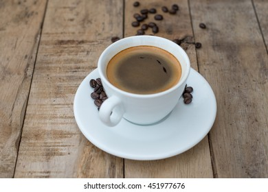 Cup of coffee and coffee beans on wooden background.