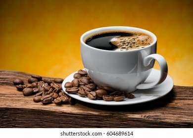 Cup of coffee and coffee beans on a wooden table