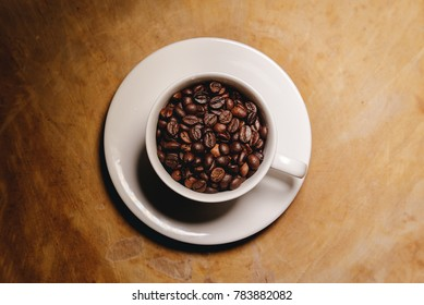 Cup of coffee beans on a wooden table