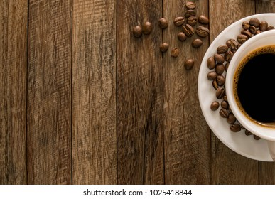 A cup of coffee and coffee beans placed on a wooden background.