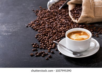 cup of coffee and coffee beans in a sack on dark background
