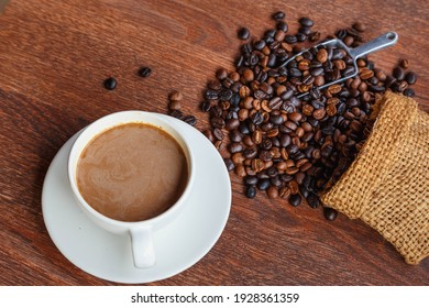 cup of coffee and coffee beans in a sack on  Brown background, top view