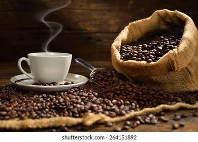 Cup of coffee and coffee beans with smoke on old wooden table, This photo is available without smoke