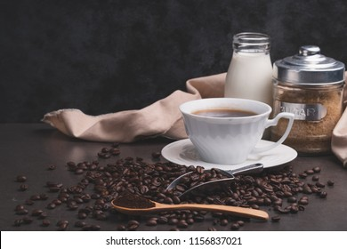 Cup of coffee with coffee beans, spoon, a bottle of milk and sogar on brown background