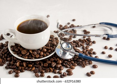 a cup of coffee ,coffee beans and stethoscope on white wooden background  in concept Health of coffee drinkers, quality of coffee