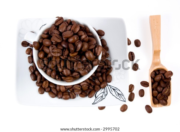 Cup with coffee beans and wooden spoon isolated on white.