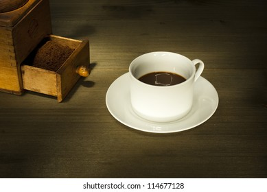 cup of coffee and coffee beans, wooden table