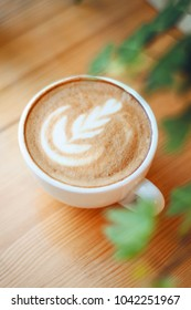 A cup of coffee with beautiful Latte art on wooden background table. Relax on weekend concept. Coffee cup in coffee shop
