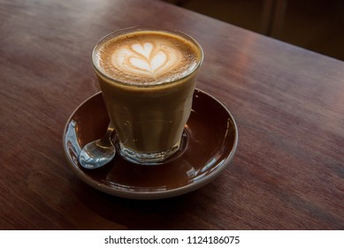 Cup of coffee with beautiful latte art on wood background