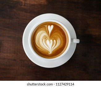 Cup of coffee with beautiful latte art on wooden table