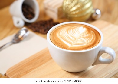 Cup of coffee with beautiful Latte art and coffee beans on wooden background