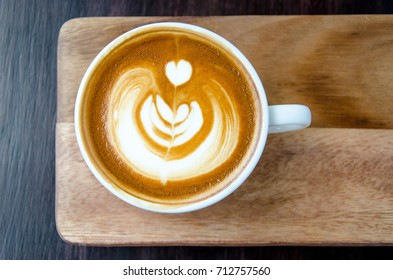 Cup of coffee with beautiful Latte art on wood plate with black background.
