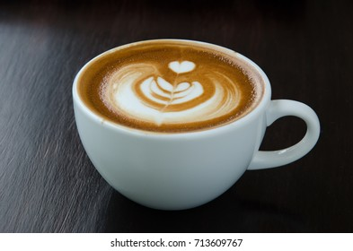 Cup of coffee with beautiful Latte art on black background.