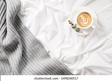 Cup of coffee in bed. Cozy autumn flatlay. Cappuccino and morning routine. Copy space. Concept minimalism