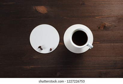 Cup of coffee and beer coaster on wood table background. Flat lay.