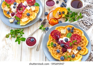 Cup of coffee and Belgium waffles with blueberry, blood orange,  whipped cream, jam, mint and white chocolate on wooden table. Breakfast concept.