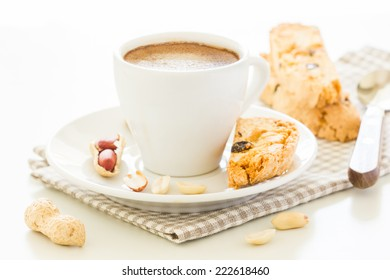 Cup of coffee and biscotti with peanut and raisins