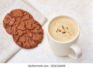 Cup of coffee and biscuit isolated on the white background, close-up, shallow depth of field.