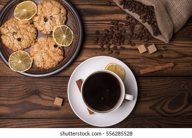 A cup of coffee with biscuits, coffee beans, cinnamon and sugar on a wooden table