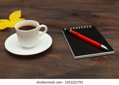 Cup of coffee, black pocketbook, pen and autumn yellow leaf on a wooden table