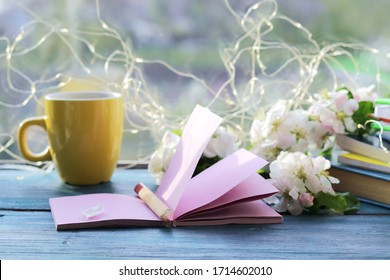 Cup of coffee, blank notebook for notes, a stack of books, apple flowers on a wooden windowsill, home comfort concept