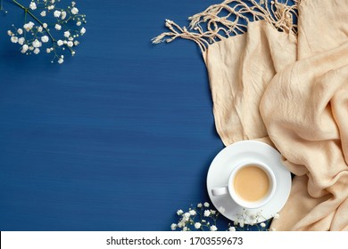 Cup of coffee, blanket and flowers on dark blue background. Cozy home desk, hygge, happy morning concept. Flat lay, top view